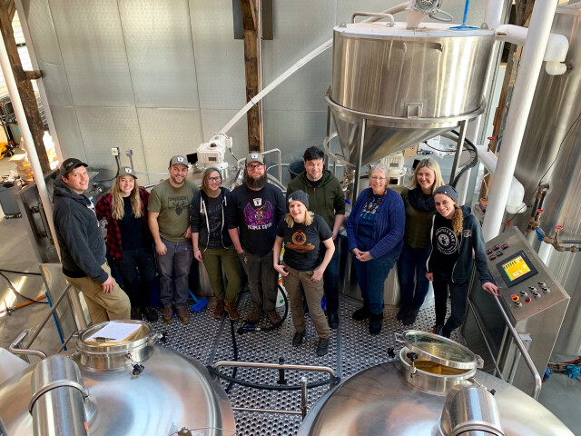 The Drekker staff and Food of the North co-founders in front of brewing equipment at the Brewhalla